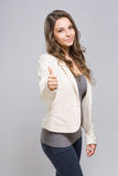 Brunette showing big thumbs up. Portrait of elegant young brunette showing big thumbs up stock image