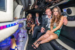 Portrait of elegant young couple with friends talking in limousine royalty free stock photos