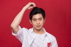 Portrait of elegant young handsome asian man over red background. Cool fashion male model. Stock Photography