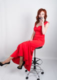Portrait of Elegant young redhead woman in a red dress, having a glass of red wine Royalty Free Stock Photography