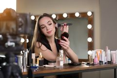 Optimistic girl is filming video for her beauty blog stock photos