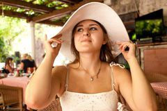Portrait of elegant young woman in white hat sitting at cafe Stock Photo