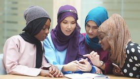 Portrait of elegantly dressed Muslim girls looking at the hands of one of her friends. Portrait of elegantly dressed caucasian and african muslim female friends stock video
