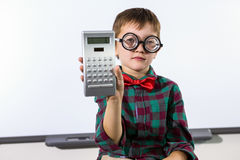 Portrait of elementary boy holding calculator in classroom Stock Image