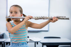 Portrait of elementary girl playing flute in classroom Stock Photos