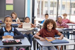 Portrait of elementary school pupils sitting at their desks Stock Photography