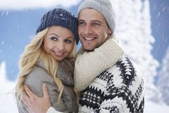 Portrait of embracing loving couple in snowfall Stock Photography