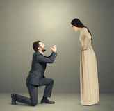 Portrait of emotional couple. Full length portrait of emotional couple over grey background. angry women looking at man, men standing on knee and apologizing Stock Images