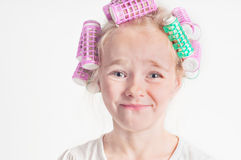 Portrait of emotional cute little girl with curler Royalty Free Stock Image