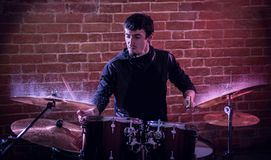 Portrait of emotional drummer rehearsing on drums. Stock Photography