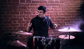 Portrait of emotional drummer rehearsing on drums before rock co Stock Photos