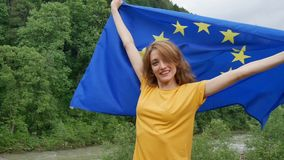 Portrait of emotional girl with the flag of the European Union which is going to study in EU smiling and looking at the. Camera on green forest background stock video