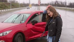 Portrait of a emotional girl who got into a car accident on the road in the rain. Portrait of an emotional girl who got into a car accident, she stands near his stock footage