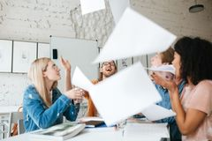 Emotional people happily throw up papers in office while working together. Group of young students joyfully studying stock images