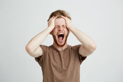 Portrait of emotional upset angry man shouting screaming holding head over white background. Royalty Free Stock Images