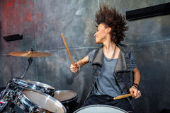 Portrait of emotional woman playing drums in studio. Drummer rock concept Stock Images