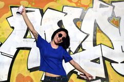 Portrait of an emotional young girl with black hair and piercings. Photo of a girl with aerosol paint cans in hands on a graffiti wall background. The concept stock photo