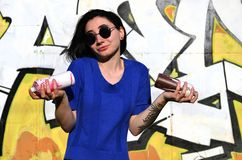 Portrait of an emotional young girl with black hair and piercings. Photo of a girl with aerosol paint cans in hands on a graffiti wall background. The concept royalty free stock photo