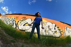 Portrait of an emotional young girl with black hair and piercings. A wide-angle photo of a girl with aerosol paint cans in the hands on a graffiti wall royalty free stock photo