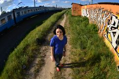 Portrait of an emotional young girl with black hair and piercings. A wide-angle photo of a girl with aerosol paint cans in the hands on a graffiti wall royalty free stock images