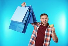 Portrait of emotional young man with credit card and shopping bags on color background. Spending money stock photography