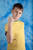 Portrait of emotionally kid. Angry child show fist. Portrait of emotionally kid. Angry child show his fist. Blue background stock image
