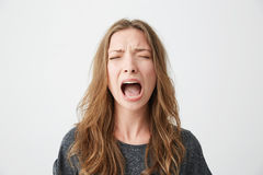 Portrait of emotive young beautiful girl shouting with closed eyes over white background. Copy space stock images