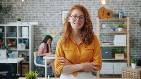 Portrait of employee looking at camera and smiling in office with arms crossed. Portrait of beautiful female employee looking at camera and smiling standing in stock footage
