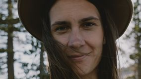Portrait en gros plan atmosphérique de jeune belle fille de sourire dans le chapeau avec des cheveux de vol au mouvement lent de  clips vidéos
