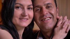 Portrait en gros plan d'étreindre les conjoints arabes observant smilingly dans la caméra avec leurs enfants sur le fond clips vidéos