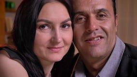 Portrait en gros plan d'étreindre les couples arabes observant smilingly dans la caméra avec leurs enfants sur le fond clips vidéos