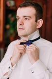 Portrait en gros plan d'homme d'affaires bel dans le costume bleu mettant sur le noeud papillon à l'intérieur Photos stock