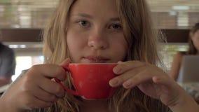 Portrait en gros plan d'un café potable de matin de fille blonde sexy en café La femme de charme boit du cappuccino du rouge banque de vidéos