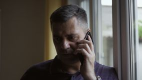 Portrait en gros plan d'un homme parlant au téléphone se tenant à l'intérieur à la fenêtre banque de vidéos