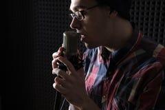 Portrait en gros plan d'un jeune homme chantant avec les yeux fermés en verres et d'un chapeau tenant un microphone dans sa main photos stock