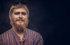Portrait en gros plan d'un mâle barbu beau de sourire dans une chemise démodée sur un fond foncé image libre de droits