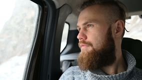 Portrait en gros plan d'un mâle barbu de hippie s'asseyant dans la voiture dans la banquette arrière et méditant tout en regardan clips vidéos