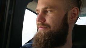 Portrait en gros plan d'un mâle barbu de sourire de hippie s'asseyant dans une voiture dans le siège arrière et méditant tout en  banque de vidéos