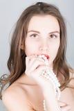 Portrait en gros plan d'une belle fille avec les lèvres rouges, tenant un collier de perle la bouche ouverte, perle des contacts  photos stock