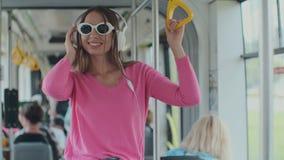 Portrait en gros plan d'une jeune femme avec des écouteurs se tenant dans le tram moderne Une femme en verres écoute la musique d clips vidéos
