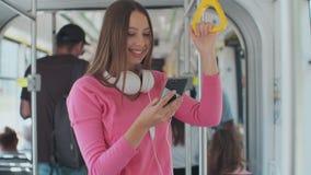 Portrait en gros plan d'une jeune femme ? l'aide du smartphone tout en se tenant dans le tram moderne clips vidéos