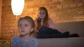 Portrait en gros plan dans le profil de deux filles caucasiennes observant le film attentivement en atmosphère à la maison confor banque de vidéos