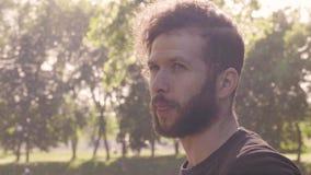 Portrait en gros plan dans un profil d'un jeune homme barbu qui lisse sa barbe et cheveux slowmo de la vue de côté 4K banque de vidéos