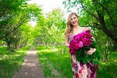 Portrait en gros plan de beauté de jeune jolie fille avec la pivoine de fleur utilisant le rouge à lèvres rose lumineux, touchant Photos libres de droits