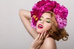 Portrait en gros plan de beauté de jeune jolie fille avec des fleurs dedans il Photos stock