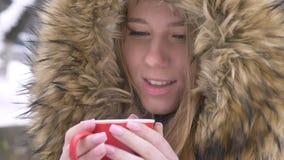 Portrait en gros plan de belle jeune fille caucasienne avec la tasse de boisson chaude et de sourire dans la caméra sur la rue d' banque de vidéos