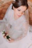Portrait en gros plan de belle jeune mariée dans la robe de mariage se reposant sur le tapis et tenant le boutonniere floral mign Images stock