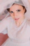 Portrait en gros plan de belle jeune mariée sensuelle dans la robe de mariage soulevant et sa fourmi de voile regardant l'apparei Photographie stock