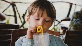 Portrait en gros plan de cocktail potable de milkshake de petit garçon européen mignon heureux avec une paille en café moderne de banque de vidéos
