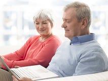 Plan rapproché d'un couple supérieur utilisant l'ordinateur portable Image stock